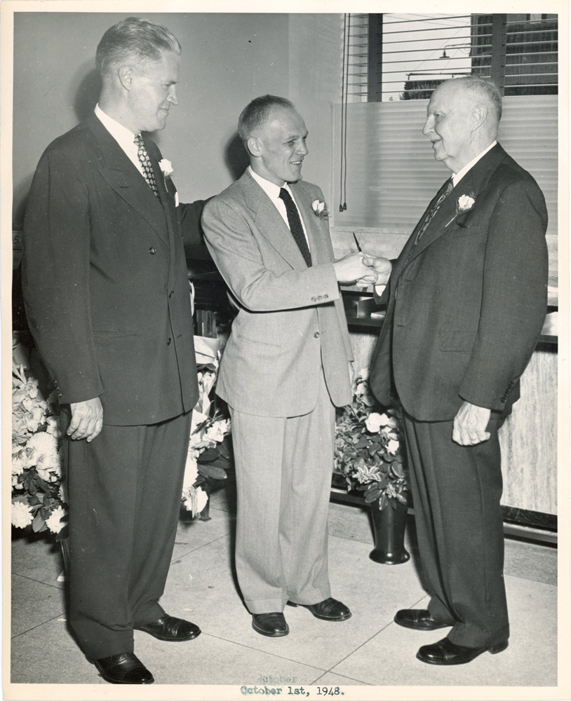 Three men in suits have a conversation inside the Laurelton branch.
