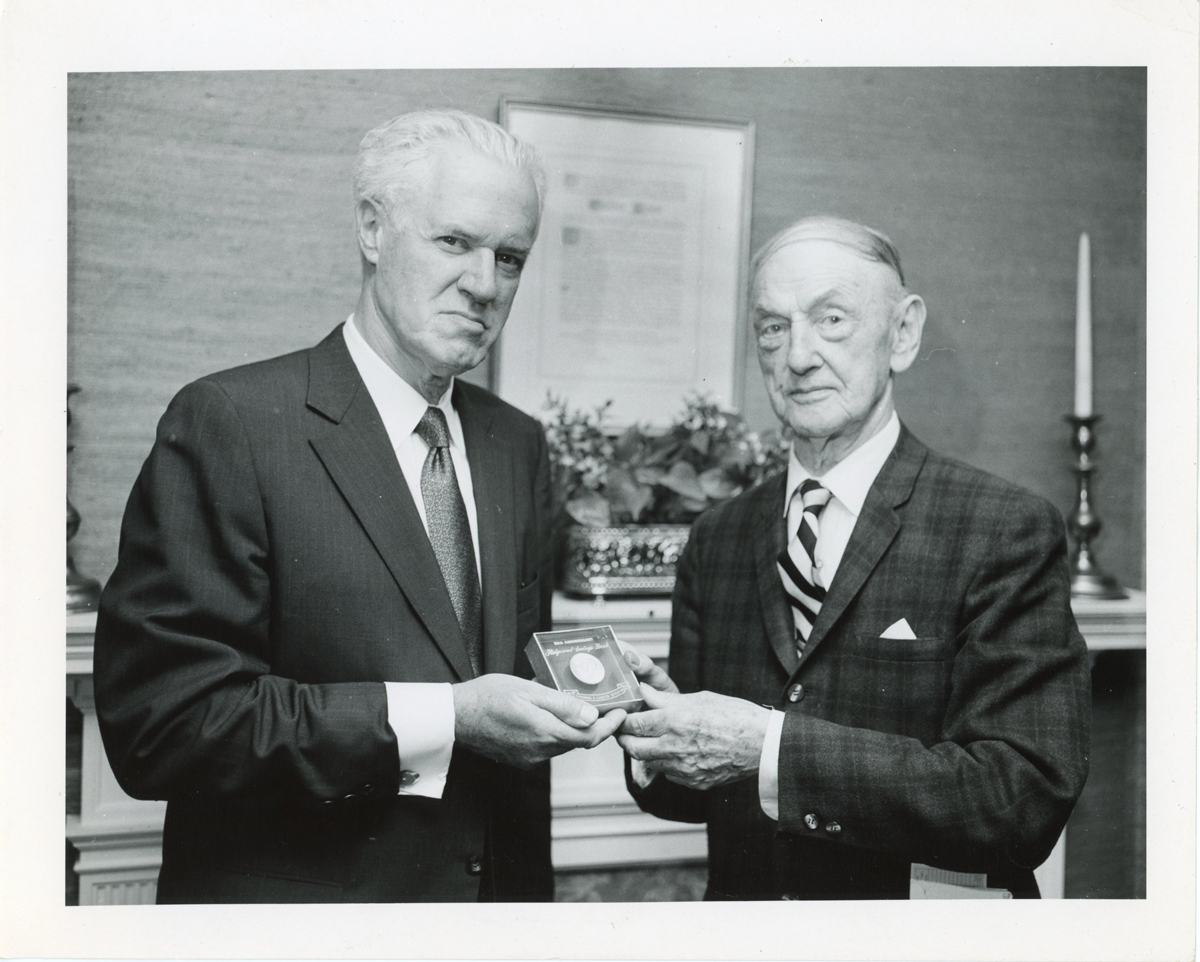 Three men in suits holding up an award
