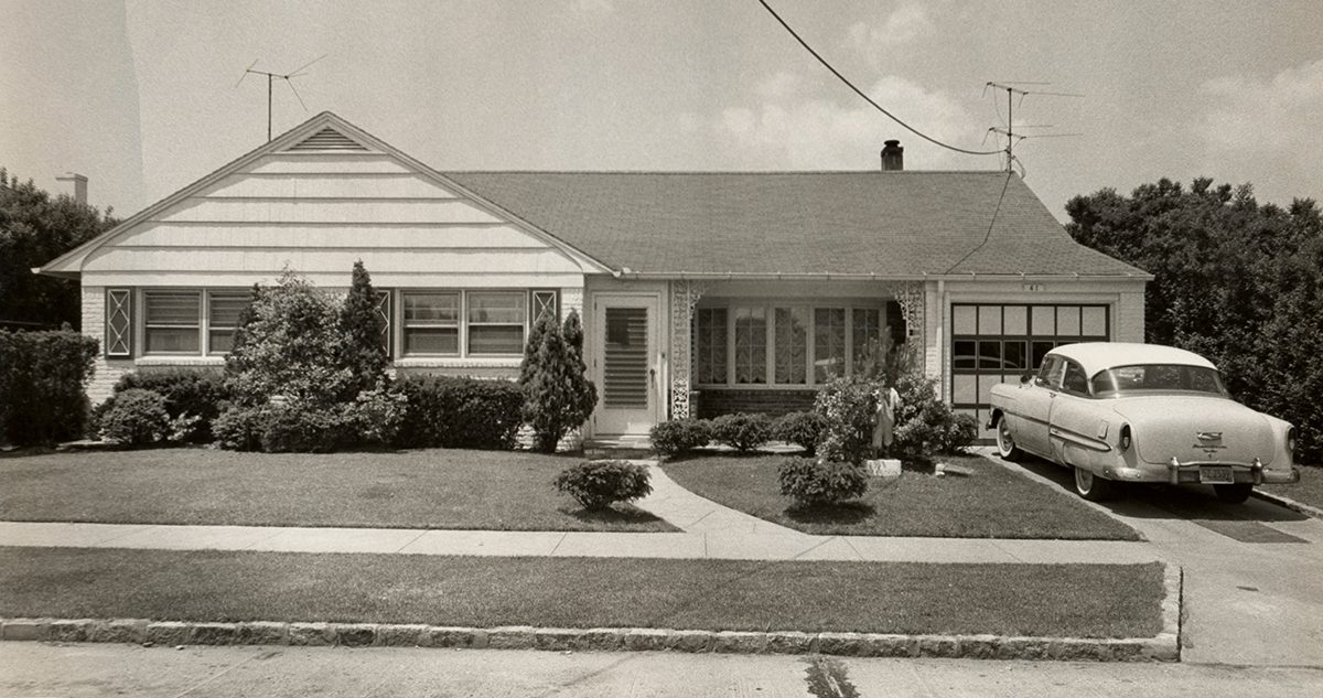 Black and white photo of a suburban home with a car parked in the driveway