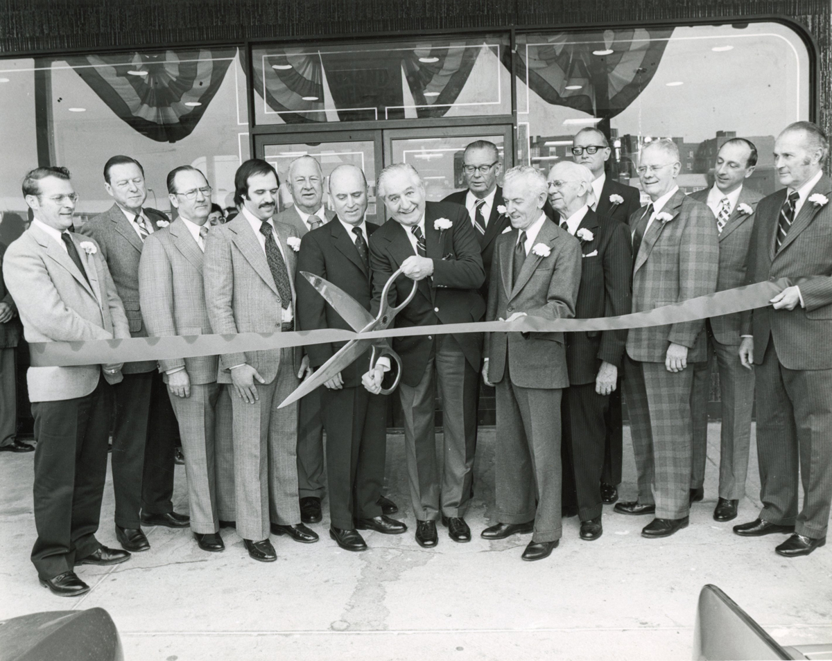 Ridgewood's team uses oversized scissors to cut a ribbon at a branch grand opening