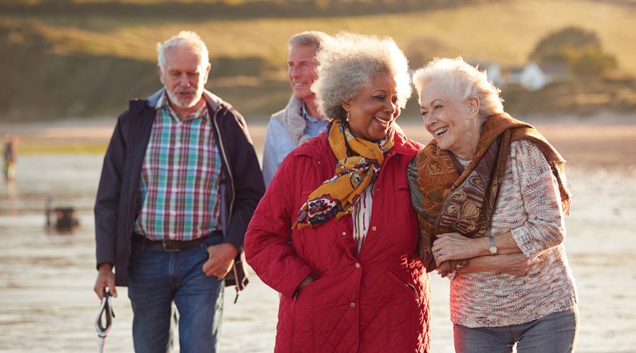 Two couples walking on the beach enjoying retirement.